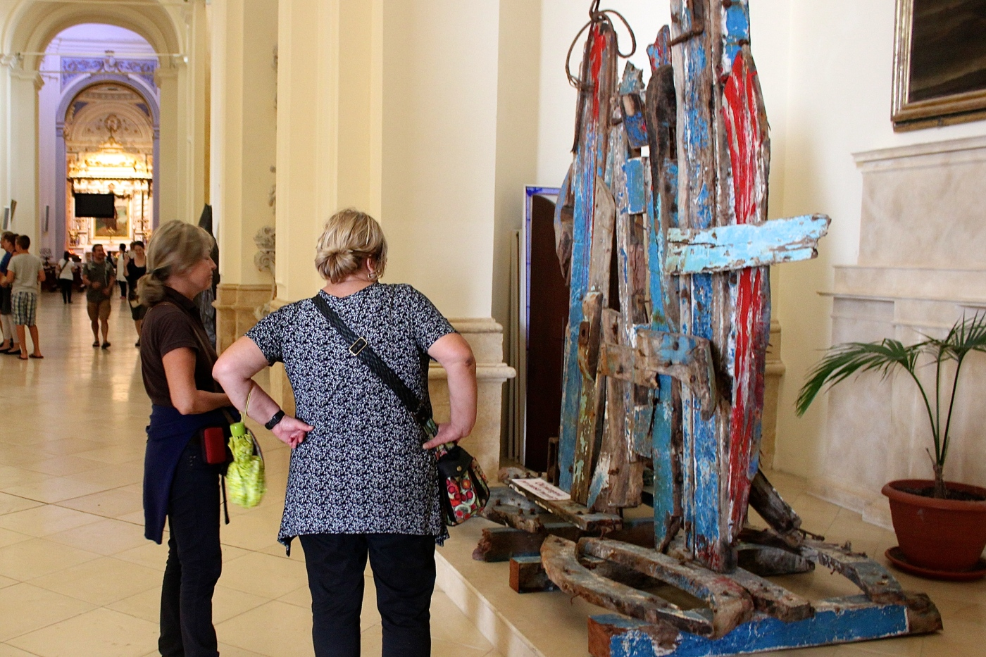Tourists consider a sculpture made of boards from a migrant boat in a Sicilian cathedral.
